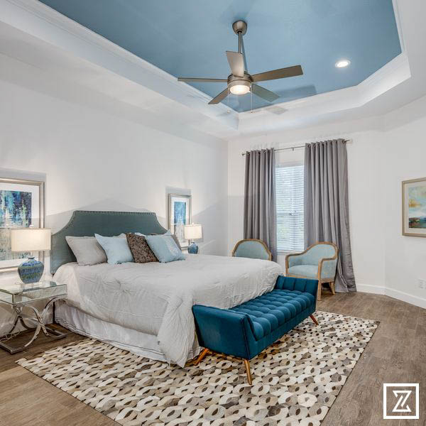 Stone Crest master bedroom - blue tray ceiling, king-sized bed with grey bedspread, grey area rug