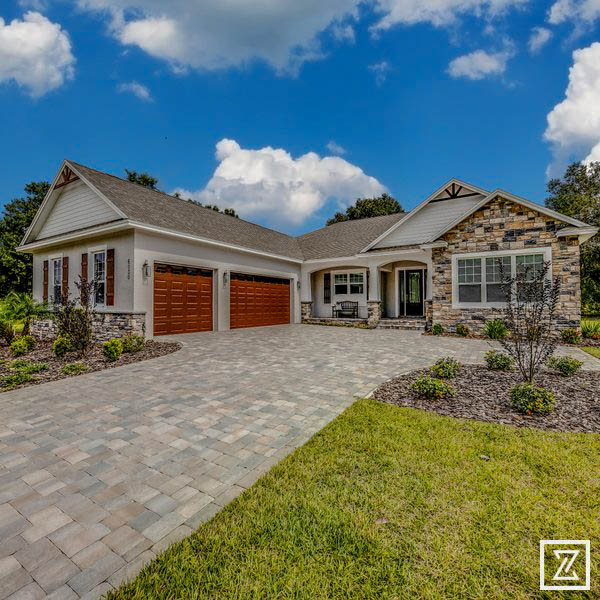 Stone Crest - front elevation, long paver driveway, 2 red garage doors, stucco and stone exterior