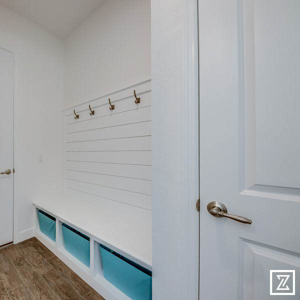 Stone Crest mud room - white plank wall and bench, cyan bins